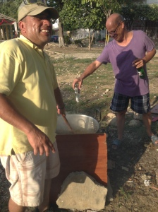 Miguel's neighbor Antonio stirs the Natilla while his other neighbor adds some Aguardiente